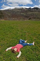 little girl lying on the back in meadow, Alps, France, Europe.