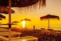 Beach hammocks at sunrise, Benalmadena. Malaga province Costa del Sol. Andalusia Southern Spain, Europe.