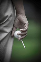 Golfer Holding a Golf Ball and a Tee in Switzerland.