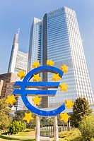 euro symbol in front of eurotower european central bank building in frankfurts central business district, frankfurt am main, hesse, germany.