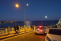 people look over Bondi Beach on moonlit evening, Sydney.