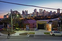 Neutral Bay street with view of North Sydney corporate skyline at dusk.