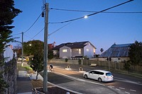 car follows cyclist on hilly suburban street at dusk, Sydney.