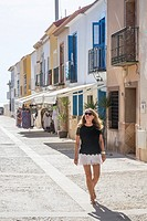 Solo femail tourist walks down the main street of the Spanish island of Tabarca.