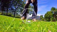 Golfer Making a Golf Swing and Hitting the Golf Ball on Wet Grass in Ticino, Switzerland.