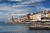 Young people sunbathing on dock at Piran Slovenia on the Adriatic Sea coast with 13th century Church of St Clement at Punta Lighthouse.
