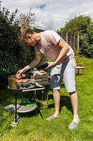 A Young Man Cooking Food On A Barbecue, Sussex, UK.
