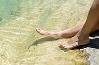 Woman rests her feet in the water of the beach, Carcaixent, Valencia, Spain