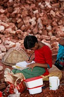 Bangladeshi Child labor reading book during the break at her work in Postogola brick breaking yard in Dhaka, Bangladesh, on June 3, 2017. With over ha...