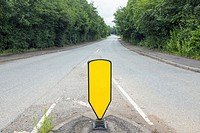 Empty road with yellow traffic sign in Cheshire UK.