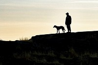 Silhouette of a man and his dog at Cattle Point, Uplands Park, Oak Bay, Victoria, Vancouver Island, British Columbia, Canada.