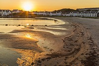 Town of Port Ellen, shot in direct light at evening time with the sandy beach in front and houses in the background, sun making nice color in the sand...