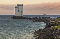 Port Ellen Lighthouse, Carraig Fhada Lighthouse in evening light after sunset with nice colors on the skye with cliffs and seaweed in foreground, Port...