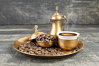 Turkish coffee with traditional copper serving set and coffee beans.