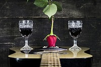 Red Rose and Wine Glasses Resting On Acoustic Guitar With Wooden Background.