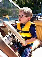 A boy pretending to drive a boat while it is parked at the dock at the Pend Oreille River, Idaho, USA.