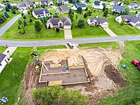 The foundation of a new home house construction in a residential neighborhood aerial view.