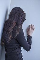 Teenage girl, back to camera, hand on a wall.