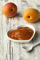 Bowl with homemade apricot jam and fresh fruit on the background.