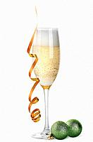 Glass of champagne and Christmas balls isolated on white background.