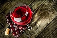 Glass of red wine with grapes on a wooden table.