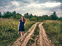 A girl with red long hair strolls along the sandy road along the forest lake. The girl's hair develops in the wind. The girl is dressed summer dress a...