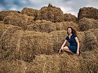 Red-haired girl in a light summer dress of blue color sits on a stack of straw. The girl's hair develops in the wind. The girl is dressed summer dress...