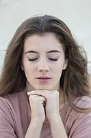 Close-up portrait of a teenage woman with closed eyes. Shot with natural light.