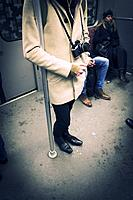 Man standing inside subway car with old analog camera. Berlin, Germany