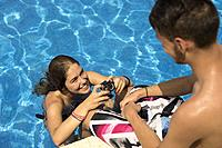 teenagers taking photos in the pool.Peñiscola, Castellon, Spain.