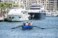 Rowing boat in the harbour at Santa Pola in Alicante Spain with large Yachts moared in the background.