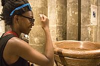 African american teen with blue sunglasses on her head is dipping her hand in holy water. She is doing the cross sign on her face in a catholic church...