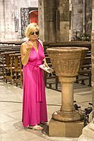 Blond retired senior blond woman with a pink sexy dress and with her sunglasses on. She is dipping her hand in holy water. She is doing the cross sign...