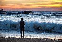 Man fishing from the beach of Atlantic Ocean in Foz do Douro district of Porto city, second largest city in Portugal.