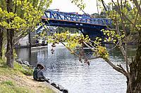 Seattle, Washington: Young couple sitting along the Fremont Cut near the Fremont Bridge. The double-leaf bascule bridge connects Seattle's Fremont and...