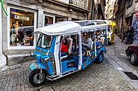Tuk Tour vehicle on a narrow street in Ribeira district in old part of Porto city on Iberian Peninsula, second largest city in Portugal.