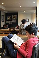 Boy,10 years old reads book in library,UK.