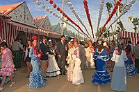 April Fair, Women wearing a traditional flamenco dress, Seville, Region of Andalusia, Spain, Europe.