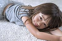 Five year old girl laying on the carpet in her room.
