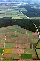 Aerial view of a windfarm and wind turbines in the middle of agricultural farmland with green fields, forest and a highway passing, Lower Saxonia, Ger...
