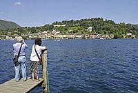 couple of tourists and Orta San Giulio, Lake Orta, Piedmont, Italy