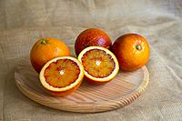 Four blood oranges, one of them cut in two halves. Still life.