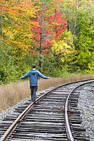 Man balancing on the railroad tracks of the old Maine Central Railroad in Carroll, New Hampshire USA.