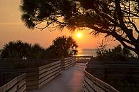 Sunset over walkway to beach on Gulf of Mexico in Venice Florida.