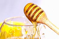 wooden spoon squirting honey from a cup of glass