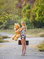 Teen girl standing waiting on country-road big teddy-bear in hand