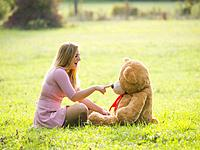 Cute teen girl and big teddy-bear toy in nature touch tip nose