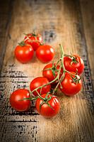 Fresh cherry tomatoes on wooden background, France.