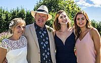 A couple, 65, with young women, 25, and 21, at an outdoor wedding in West Vancouver, BC, Canada.