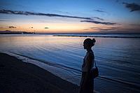 A young woman walk along the seashore at dusk, Gili Air, Gili Islands, Indonesia.